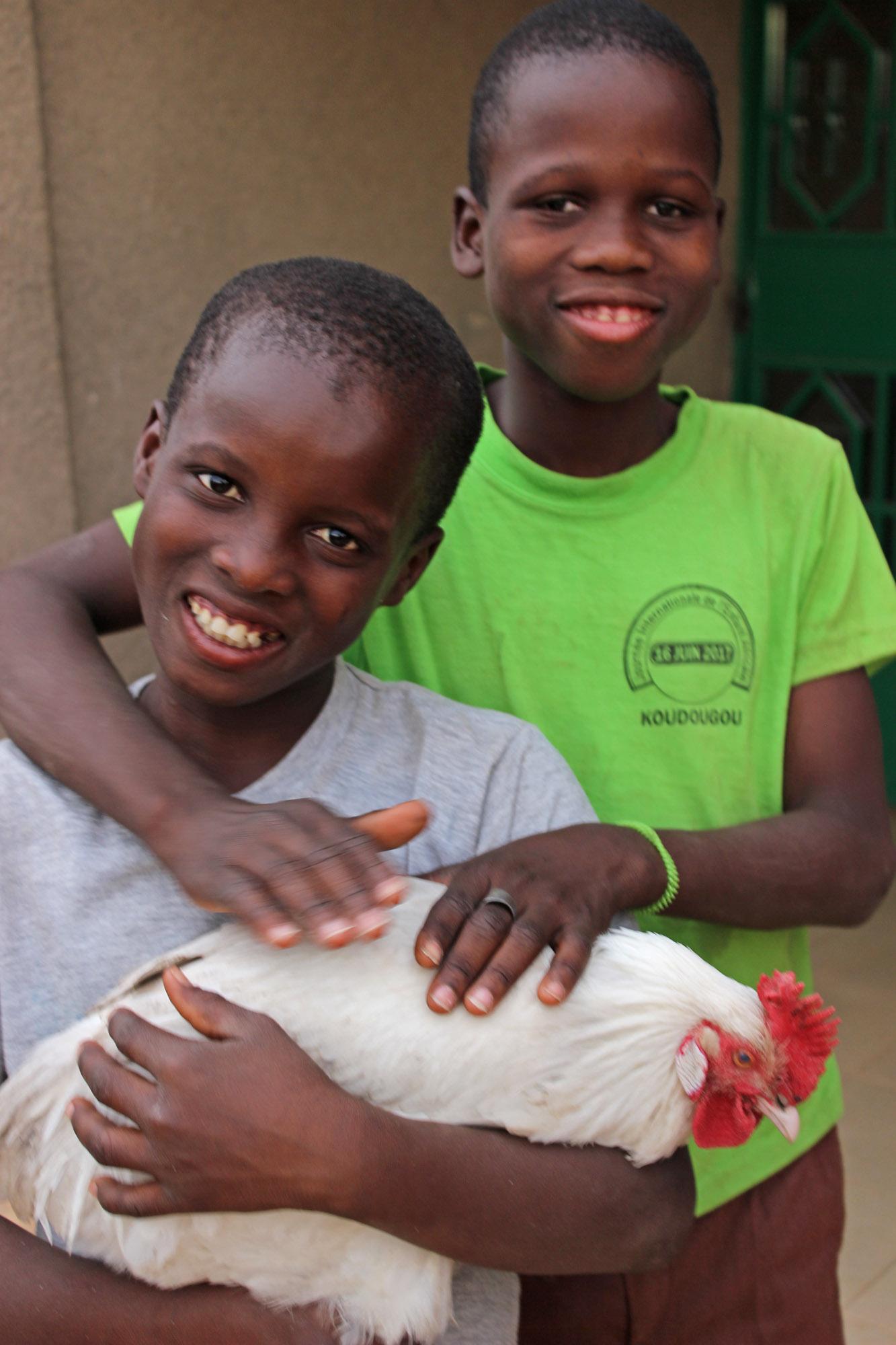"""Der Hahn """"Edi"""", den wir geschenkt bekamen, in der Obhut der Kinder des Waisenhauses in Lattou"""